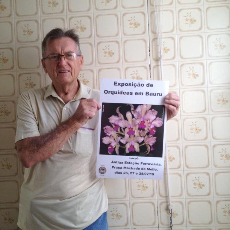 Edwin Wittmann com cartaz de divulgação da Exposição de Orquídeas. (Foto: Divulgação/Prefeitura Municipal de Bauru)