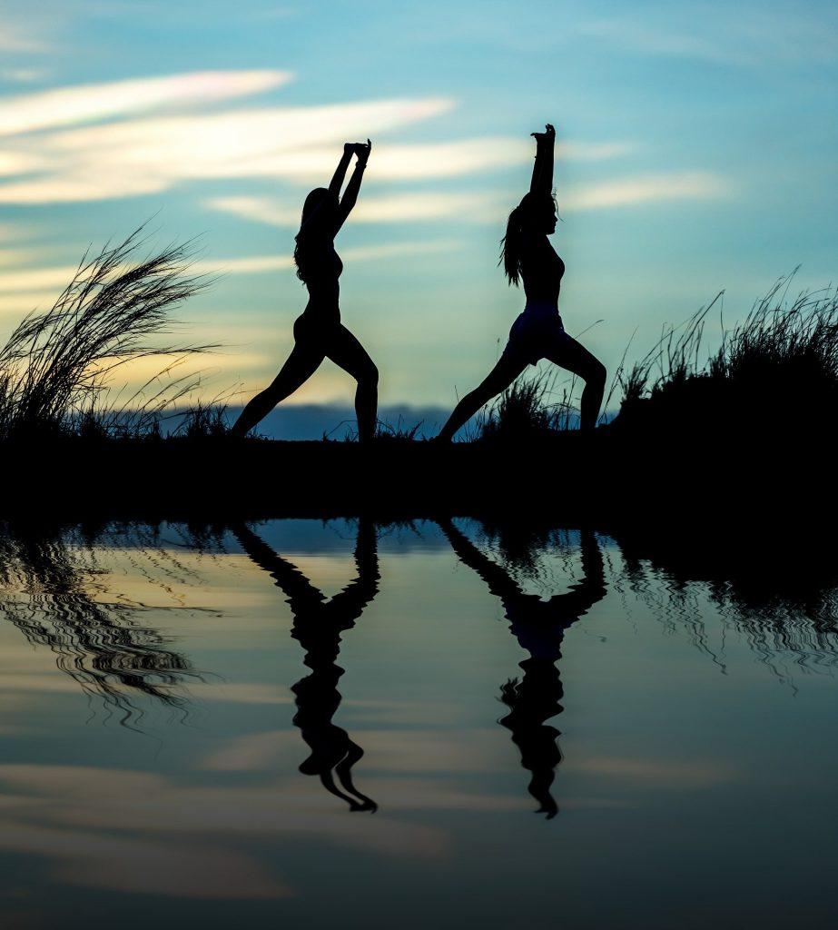 Penumbra de duas mulheres praticando yoga na beira de uma lagoa, ao por do sol.