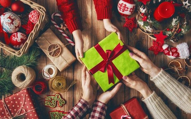 Imagem com mãos segurando um presente de Natal em uma superfície decorada com motivos natalinos. Dá para economizar no presente e fazer todo mundo feliz!