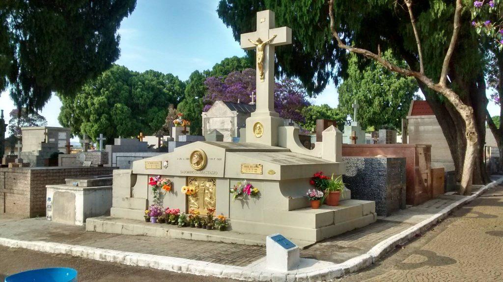 Foto colorida do túmulo de Domingos Anastácio no Cemitério Nossa Senhora do Desterro. O túmulo está com alguns vasos de flores, de visitantes.