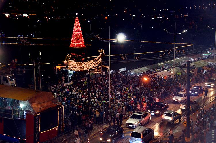 Foto da chegada do Papai Noel com grande multidão e a árvore de natal no Parque da Cidade durante o 'Natal no Parque'.