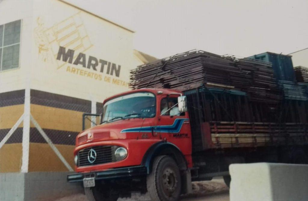 Caminhão vermelho carregado de esquadrias de ferro, saindo da Martin.
