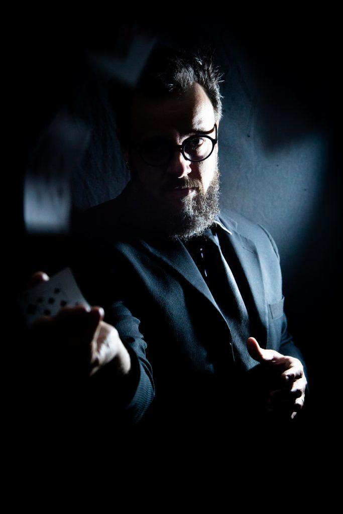 William, em uma foto escura, com terno também escuro, jogando cartas.