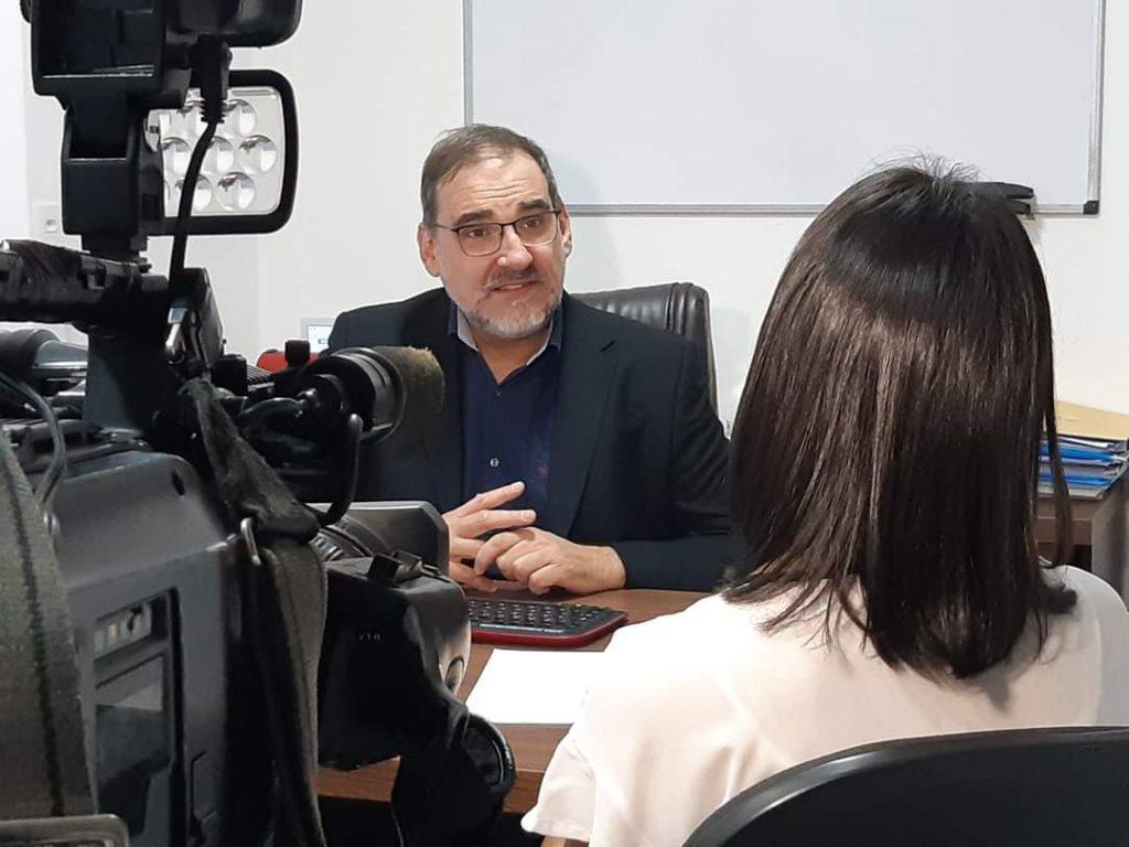 Fotografia de Pedro durante uma entrevista para a TV: à esquerda uma câmera, no centro pedro olhando para a repórter, e à direita uma repórter mulher, de costas para o autor da foto.