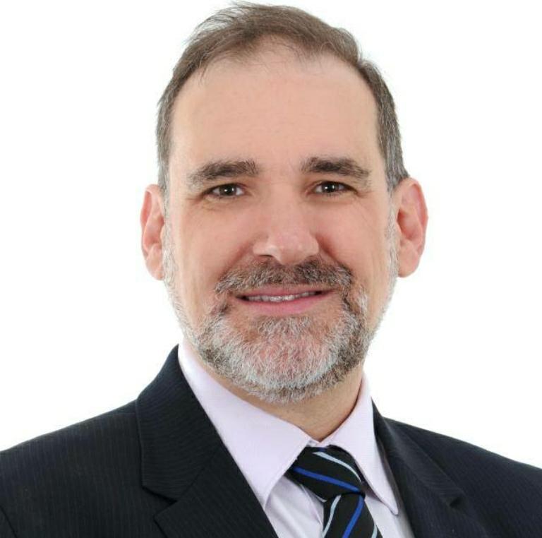 fotografia de frente do Pedro Braggio, de terno preto e gravata preta e azul.