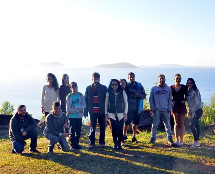 Um grupo de pessoas no alto de um monte, posando para uma foto, e atrás uma montanha com neblina.