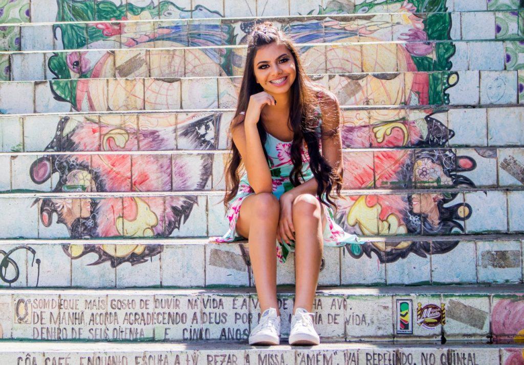 Foto de uma menina olhando para a câmera, com a mão no queixo, sentada em uma escadaria toda grafitada, parte do roteiro do Rolê Fotográfico.