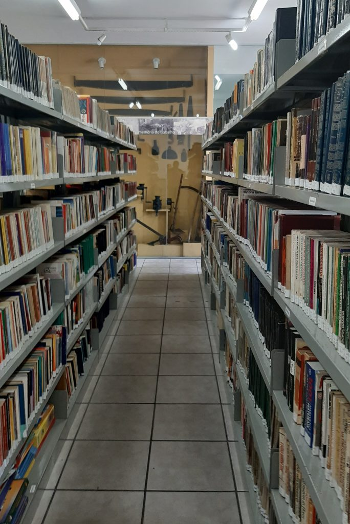 Um dos corredores da Biblioteca municipal, com estantes repletas de livros à direita e à esquerda, com uma das exposições do Centro de Memória ao fundo.