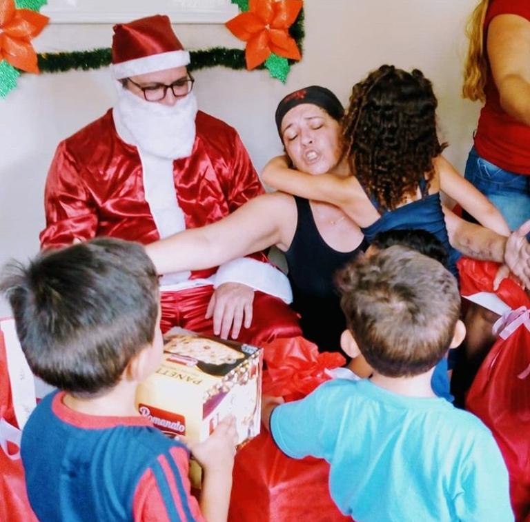 flavia, com o papai noel, abraçando crianças na festa de natal da acai