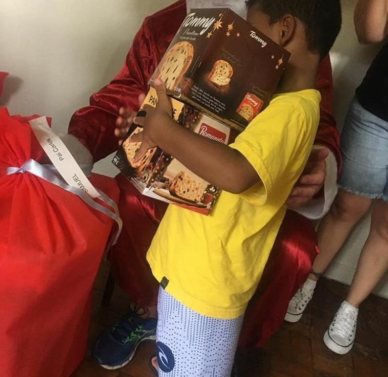 flagra da festa de natal da acai, com uma das crianças levando seus pannetones