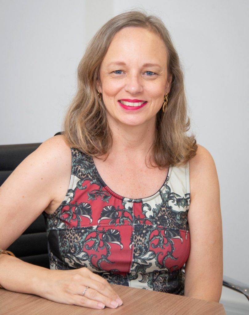 Foto de Elaine Ninzoli, responsável pela we treinamento e crescimento profissional, sentada à mesa e olhando com um sorriso para a câmera.