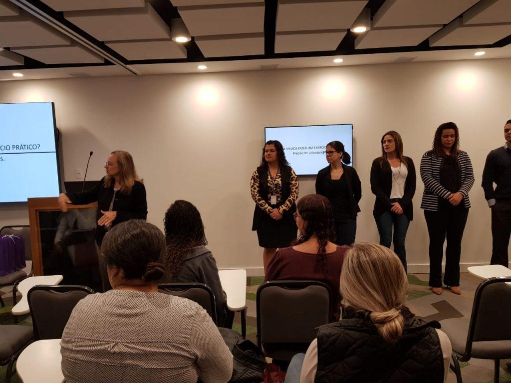 Foto de uma plateia, em primeiro plano, prestando atenção em um grupo de mulheres que estao de pé a frente, e à esquerda Elaine, responsável pela we treinamento, olhando para um telão.