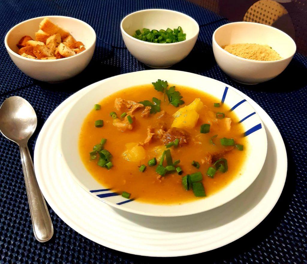 Descrição: Tigela de sopa ao lado de prato com comida  Descrição gerada automaticamente