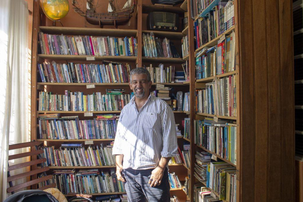 Professor e escritor bauruense José Reginaldo Furtado e uma estante de livros no fundo