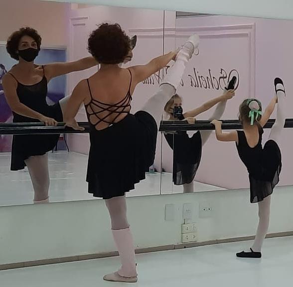 Dia da Bailarina. Na foto, uma mulher adulta e criança em uma barra de ballet executando um movimento