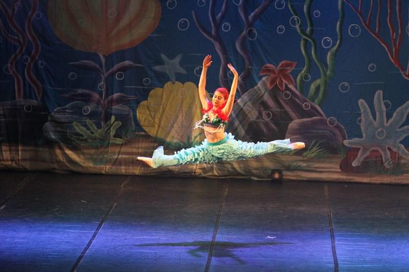 Bailarina executando salto em espetáculo da Pequena Sereia