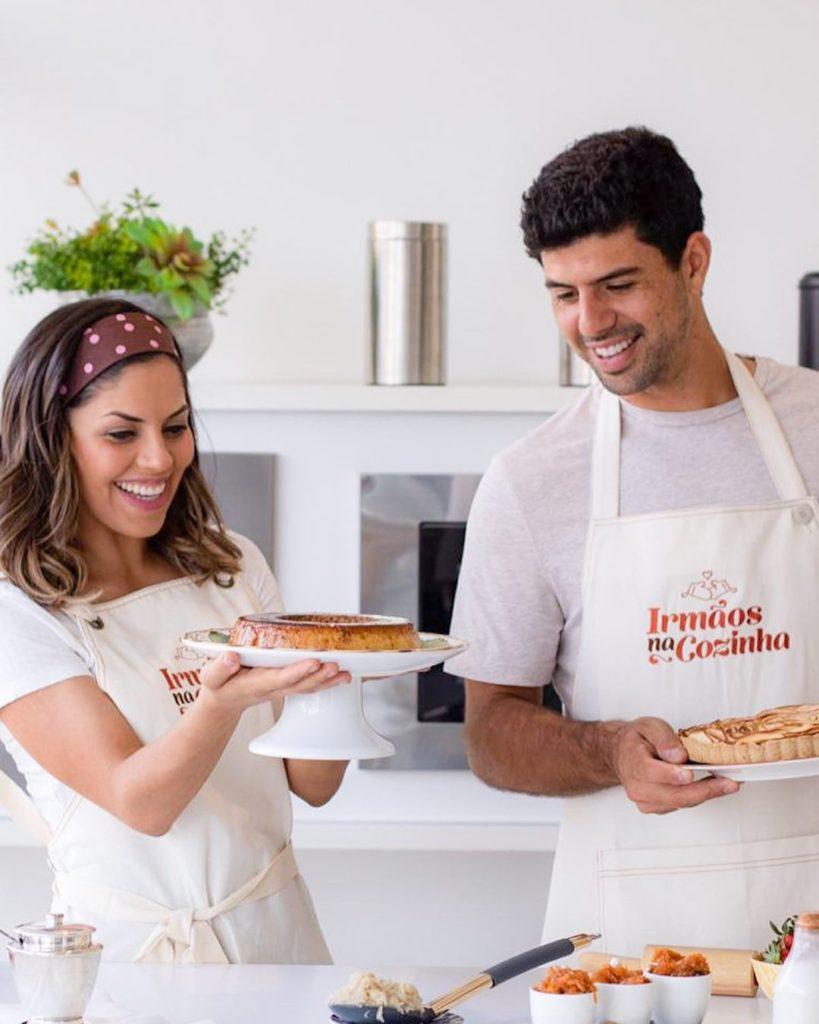 Irmãos na Cozinha: Carol e Rodolfo Bustamante. Um homem uma mulher, ambos com um avental bordado. Ela segurando uma torta.