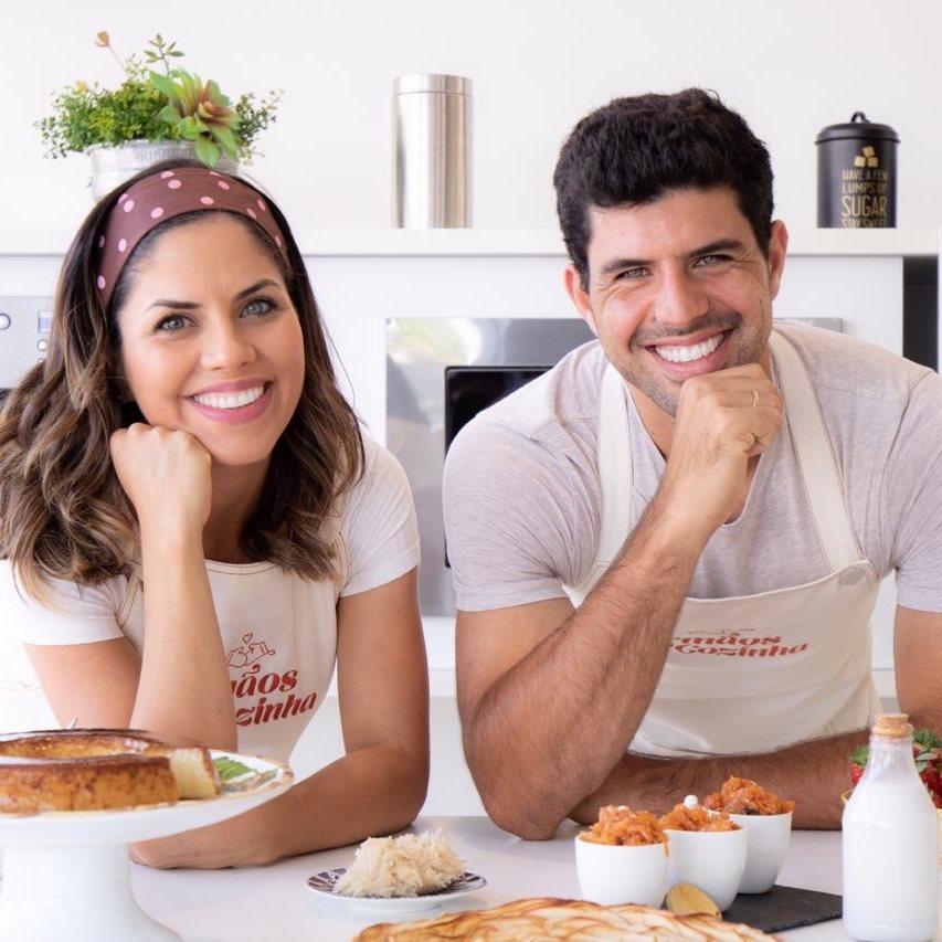 Irmãos na Cozinha: Carol e Rodolfo Bustamante. Um homem uma mulher, ambos com um avental. Os dois estão apoiados em uma bancada de cozinha,