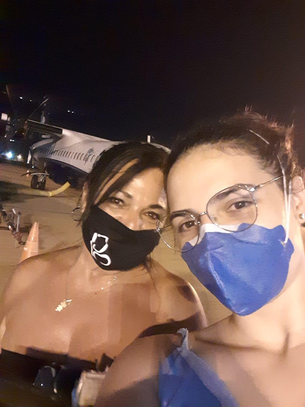 """Na foto, duas mulheres de máscaras com um avião ao fundo. Bauruense que viajou mais de 2 mil km para doar medula óssea relata sua experiência: """"Faria tudo de novo"""""""