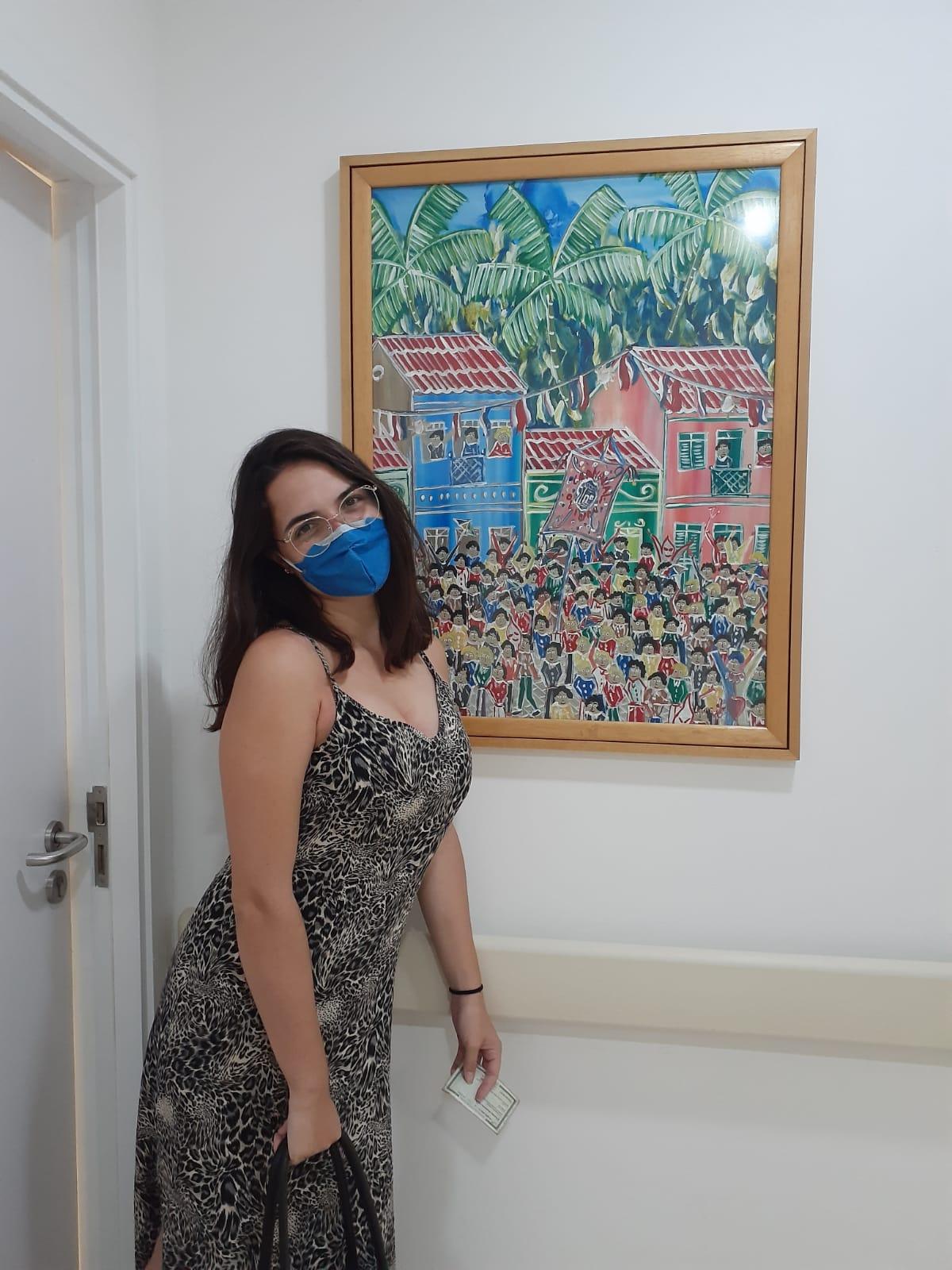 """Na foto, uma mulher de máscara em um consultório médio, na frente de um quadro colorido. Bauruense que viajou mais de 2 mil km para doar medula óssea relata sua experiência: """"Faria tudo de novo"""""""