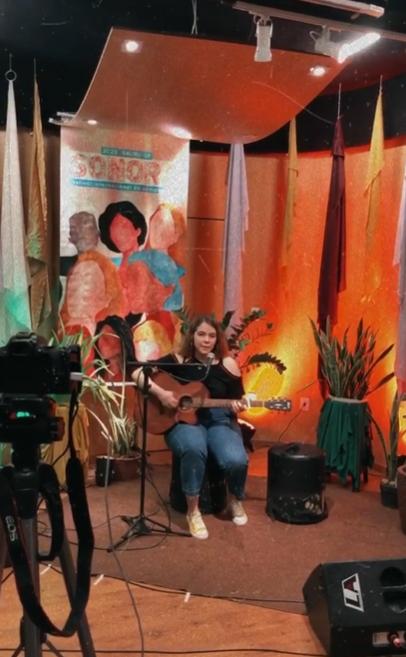 Mulheres na Música. Na foto, uma mulher sentada com um instrumento musical, tocando e cantando.