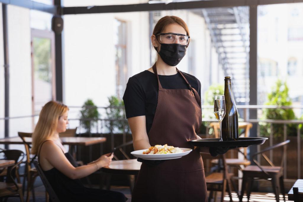 Foto: The waitress works in a restaurant in a medical mask, gloves during coronavirus pandemic. Novidades gastronômicas em Bauru: o que abriu na Cidade Sem Limites
